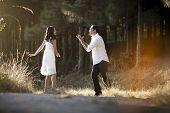 foto of flirtatious  - happy flirtatious Indian couple walking along dirt road together - JPG