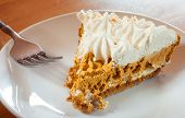 pic of pumpkin pie  - Whipped pumpkin pie slice and fork on a white plate - JPG