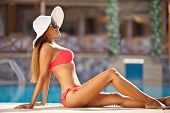 foto of sunbather  - Beautiful girl in red bikini relaxing by the pool and enjoying in sunbathing - JPG