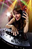 image of emcee  - caucasian female dj using a mixer and computer to play mp3s - JPG