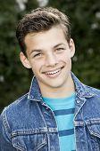 image of denim wear  - Smiling teenage boy outside wearing denim jacket vertical format 13 yrs old - JPG