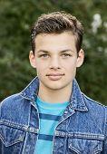 picture of denim wear  - Teenage boy outside wearing denim jacket vertical format 13 yrs old - JPG