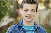 stock photo of denim wear  - Smiling teenage boy outside wearing denim jacket horizontal format 13 yrs old - JPG