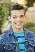foto of denim wear  - Smiling teenage boy outside wearing denim jacket vertical format 13 yrs old - JPG