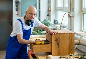 stock photo of dungarees  - worker in blue dungarees in a carpenter - JPG
