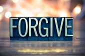 stock photo of forgiveness  - The word FORGIVE written in vintage metal letterpress type on a soft backlit background - JPG