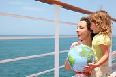 Mother And Daughter Holding Inflatable Globe On Cruise Liner