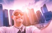 stock photo of tilt  - Handsome man taking selfie at modern urban area of Marina Bay in Singapore at sunset  - JPG