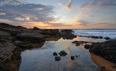 image of squirting  - Early morning skies ocean waves and incoming tidal flows over sea squirts - JPG