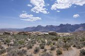 stock photo of arid  - Rugged arid valley of Red Rock national conservation area with rocky mountain peaks and desert shrubbery in late spring - JPG