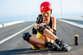 foto of sports injury  - Young sport woman with rollers in yellow skirt and red helmet having knee injury sitting on the highway - JPG