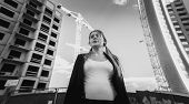 image of frustrated  - Closeup black and white portrait of frustrated and depressed woman posing against skyscrapers under construction - JPG