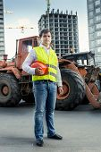 image of workplace safety  - Foreman in yellow safety jacket posing next to bulldozer on building site - JPG