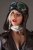 pic of licking  - woman in aviator helmet winks and licking lips isolated on gray background - JPG