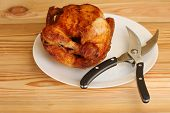 picture of poultry  - whole grilled chicken with shears for poultry on white plate on wooden table - JPG