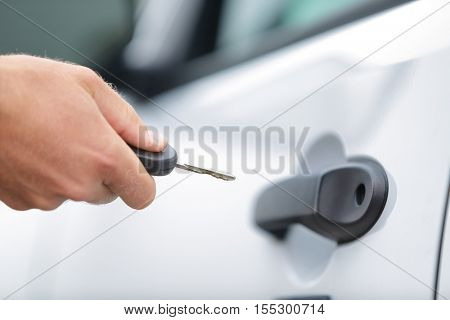 poster of Man opening unlocking door with car key. Car keys closeup of hand holding key to lock or unlock door
