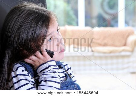 Cute Young Girl Listening Carefully On Her Cellphone Looking Serious