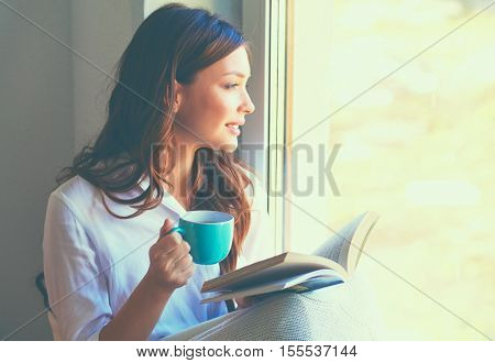 poster of Young woman at home sitting near window relaxing in her living room reading book and drinking coffee