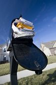 picture of soliciting  - Mailbox full of junk mail with new houses and clear blue sky in the background - JPG