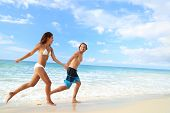 Happy beach couple vacation getaway. Young people in bikini and swimwear running holding hands toget poster