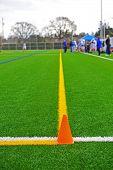 Cone & lacrosse stick on a turf field