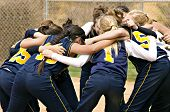 foto of softball  - Softball team huddle before the start of a softball game in color - JPG