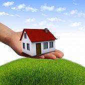 Das Haus in den Händen gegen den blauen Himmel als Symbol für das Immobiliengeschäft.