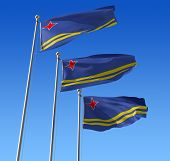 Three flags of Aruba against blue sky.