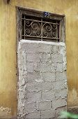 pic of cinder block  - Vintage door with decorative metal swirl pattern blocked by concrete blocks - JPG