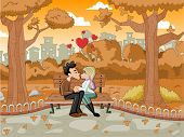 Young romantic couple passionately kissing at the park bench on autumn