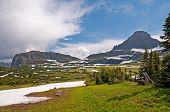 Prados, montanhas, neve e nuvens