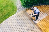 Cleaning Terrace With A Power Washer - High Water Pressure Cleaner On Wooden Terrace Surface poster