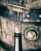 Opening wine bottle. Oak wine keg at the background. poster