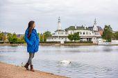 Woman walking in city park relaxing on weekend. Person enjoying lake view in Copenhagen, Denmark. Sp poster
