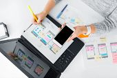 app design, technology and business concept - web designer or developer with smartphone working on u poster