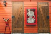 Fire Hose In Red Cabinet Hanging On Orange Wooden Wall. Fire Emergency Equipment Box For Safety And  poster