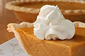 Pumpkin pie with swirls of whipped cream on decorative plate.  Whole pie in soft focus in background