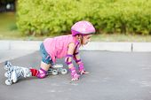 Little girl in roller skates getting up to move on
