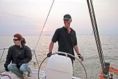Happy sailor sailing at sunset on the IJsselmeer in the Netherlands