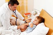a physician house call. examines sick child.