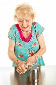 Senior woman with arthritis struggles to open a can.