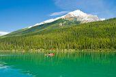 Red canoe at mountain lake. Rocky Mountains, Alberta, Canada.