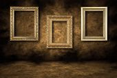 picture of dingy  - Three Guilded Picture Frames Hanging on a Grungy Wall - JPG