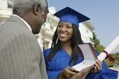 Happy young graduate student receiving gift from her father