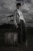 Dark moody image of a young man in a casual jacket standing alongside a vintage crate under a threat