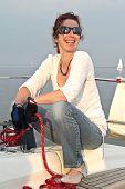 Happy dutch  woman sailing on the IJsselmeer in the Netherlands