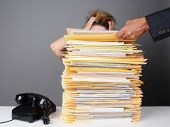 A frazzled female office worker grabs her head in frustration as her boss piles more work on her des
