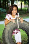 stock photo of tire swing  - Girl Outside In Her Yard On A Tire Swing  - JPG