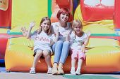 Mother And Her Daughters Sitting On Bouncing Castle