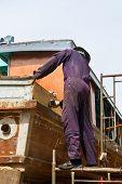 Carpenter is repairing boat in dry dock
